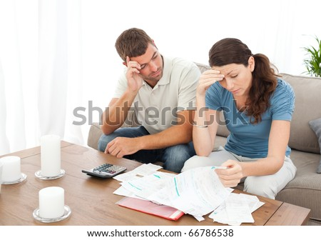 Worried couple doing their accounts in the living room at home - stock photo