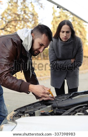 worried couple looking under the hood of breakdown car at outdoor - stock photo