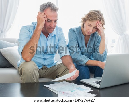 Worried couple paying their bills online with laptop at home in the living room - stock photo