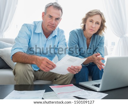 Worried couple paying their bills online with laptop looking at camera at home in the living room - stock photo