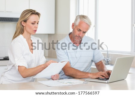 Worried couple working out their finances with laptop at home in the kitchen - stock photo