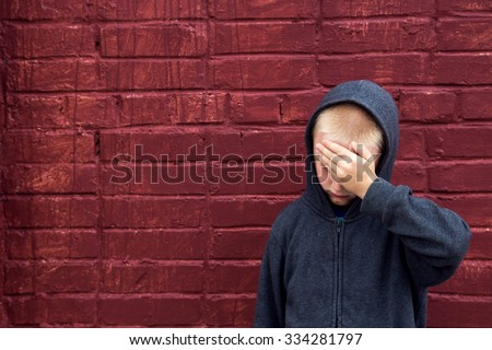 Worried depressed sad abused teen boy (child) crying near brick wall - stock photo
