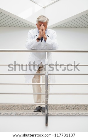 Worried doctor with face in hands leans against rail in hospital corridor - stock photo