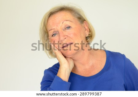 Worried elderly lady looking at the camera with her hand raised to her cheek and a pained serious expression, over grey with copyspace - stock photo