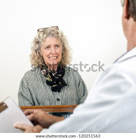 Worried frightened mature woman consults with doctor in his office. Focus is on the woman. - stock photo