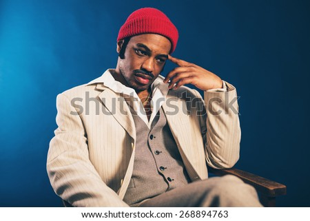 Worried handsome African American man in a stylish suit and red cap sitting staring thoughtfully at the floor with a sombre expression - stock photo