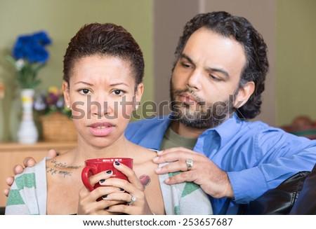 Worried hispanic couple sitting together with coffee - stock photo