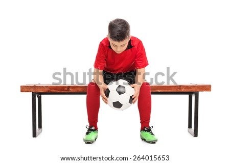 Worried little boy in red football shirt sitting on a bench and holding a ball isolated on white background - stock photo