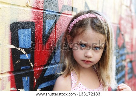 Worried little girl in an urban setting looking into the camera. - stock photo