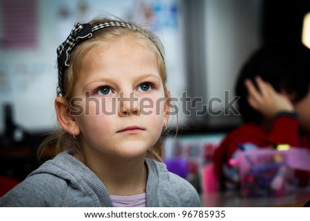 Worried little girl in school with her friends arround - stock photo