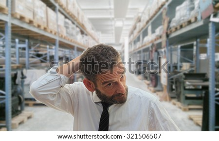 worried man at work in a storage space - stock photo