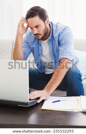 Worried man sitting at table using laptop to pay his bills in the living room - stock photo