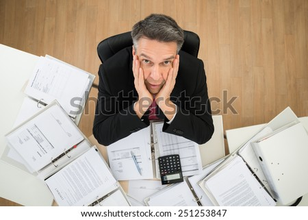 Worried Mature Businessman Looking Up With Hands On Cheek - stock photo