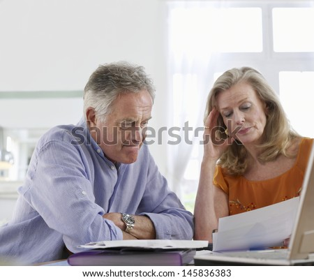 Worried mature couple with bills sitting at dining table in house - stock photo