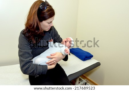 Worried mother holds her sick baby in hospital ward room. Concept photo of childhood , health care, medical treatment  and motherhood. copyspace - stock photo
