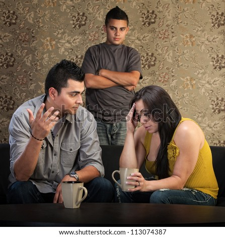 Worried Native American couple with upset son indoors - stock photo