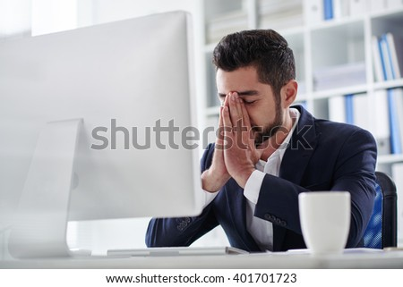 Worried or frustrated business executive in office - stock photo