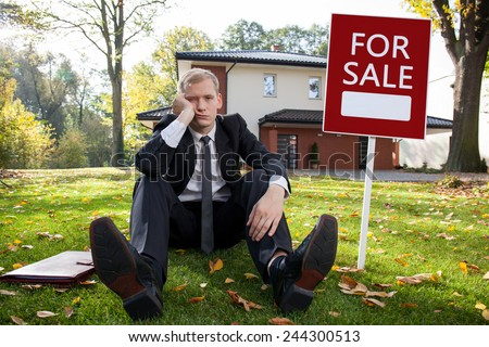 Worried real estate agent and house for sale - stock photo