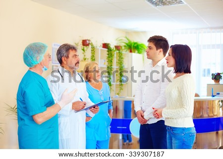 worried relatives listen to medical staff about news from difficult surgery after misadventure - stock photo