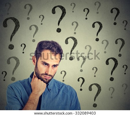 Worried sad man has many questions looking down isolated on gray wall background. Human face expression emotion feelings perception  - stock photo