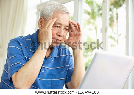 Worried Senior Chinese Man Sitting At Desk Using Laptop At Home - stock photo