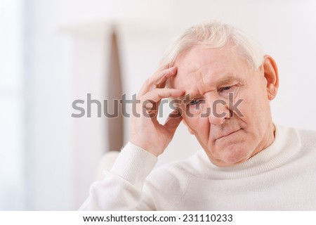 Worried senior man. Frustrated senior man touching his head while sitting in chair  - stock photo