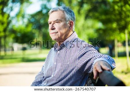 Worried senior man sitting on bench in park - stock photo