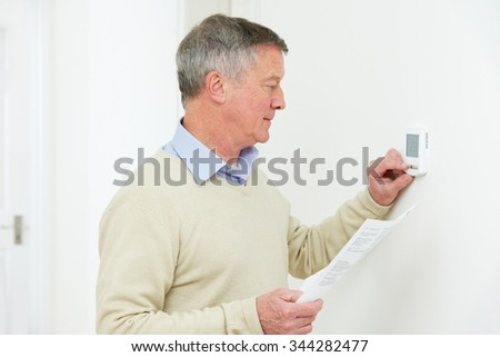 Worried Senior Man With Bill Turning Down Heating Thermostat - stock photo