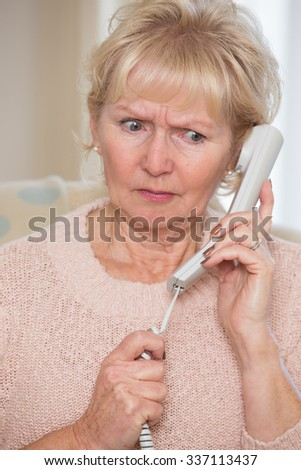 Worried Senior Woman Answering Telephone At Home - stock photo