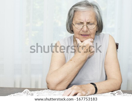 Worried senior woman sitting at the desk with hand on her chin. - stock photo