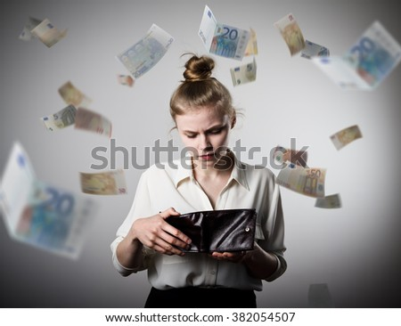 Worried slim woman is looking in a wallet. Euros are falling. - stock photo