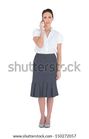 Worried stylish businesswoman on the phone on white background - stock photo