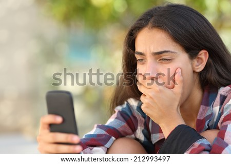 Worried teenager girl looking at her smart phone in a park with an unfocused background - stock photo