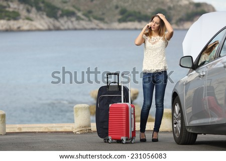 Worried traveler woman calling assistance with a breakdown car on the beach with the sea in the background - stock photo