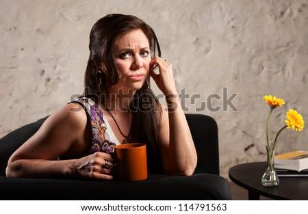 Worried woman holding coffee mug and puckering her lips - stock photo
