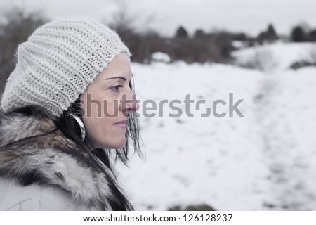worried woman in snow covered fields landscape - stock photo