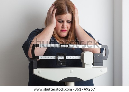 worried woman on a medical weight scale - stock photo