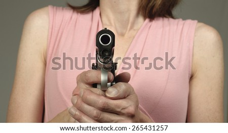Worried woman points a gun - stock photo