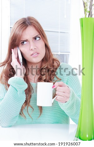worried woman receiving bad news over phone, girl holding cup of coffee and mobile phone with negative reaction - stock photo