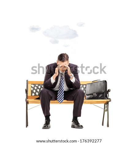 Worried young businessman sitting on bench with cloud over head isolated on white background shot with tilt and shift lens - stock photo