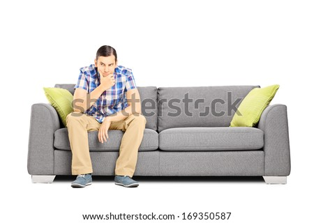 Worried young businessperson sitting on a modern sofa isolated on white background - stock photo