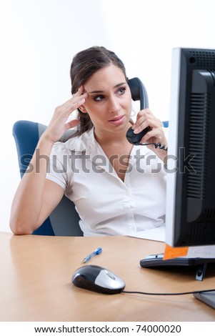 Worried young businesswoman receiveing bad news over the phone - stock photo