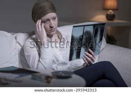 Worried young cancer woman looking at her xray photo - stock photo