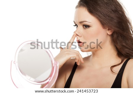 worried young woman in front of the mirror raises her nose - stock photo