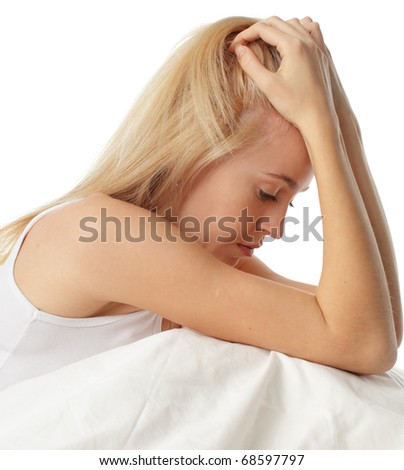 Worried young woman on bed - stock photo