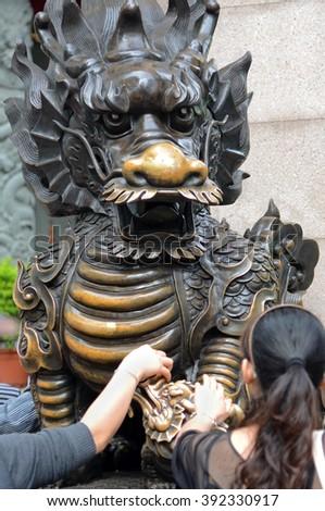 Worshippers Touching Dragon for good luck,  at Wong Tai Sin Temple, Hong Kong  - stock photo
