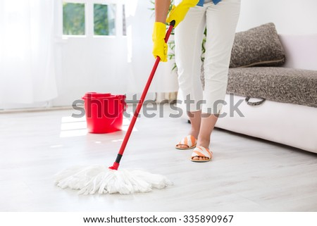 Worth housewife cleaning floor at home - stock photo