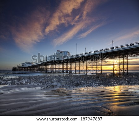 Worthing Pier reflected in wet sand at low tide, illuminated by a beautiful sunset. - stock photo