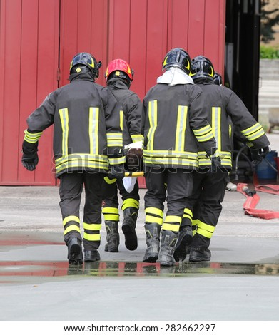 wounded carried by firefighters on a stretcher after the road accident - stock photo