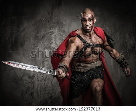 Wounded gladiator attacking with sword covered in blood  - stock photo